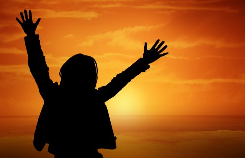 silouette of woman with raised arms against a sunrise